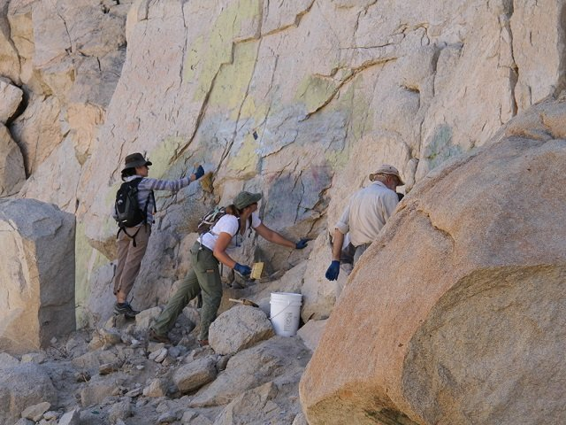 photo of volunteers removing graffiti from rock