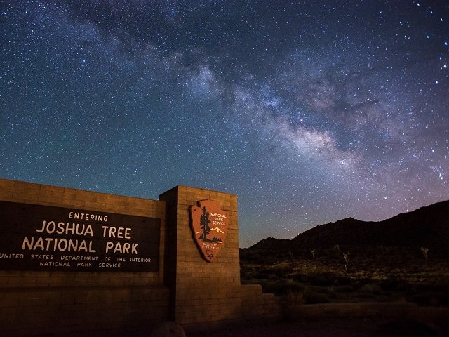 photo of the Joshua Tree National Park sign in front of the night sky