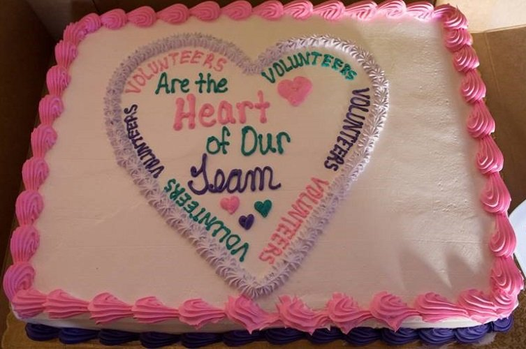 """photo of a cake that says in frosting """"Volunteers are the heart of our team"""""""